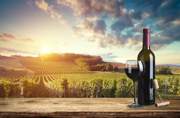 Red wine bottle and wine glass on wodden barrel. Beautiful Tuscany background Fototapete