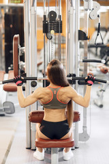 Young woman working at the lat pulldown machine in the gym,