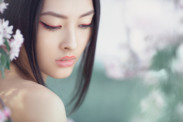 Perfect model with creative vivid makeup and pink lipstick on lips and traditional japanese hairstyle posing outside. Outdoor fashion concept photoshoot of beautiful young asian woman surrounded by