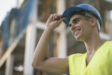 Smiling latino or caucasian dark haired construction worker touching his hardhat