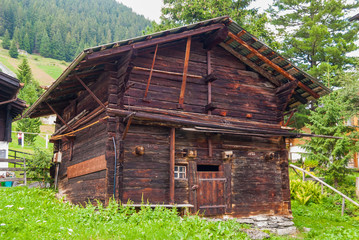 a small old wooden shed surrounded by a mountain landscape in Switzerland