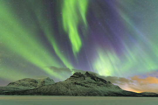 Northern Lights (Aurora borealis) on frozen lake Skoddebergvatnet, Grovfjord, Troms county, Lofoten Islands, Nordland