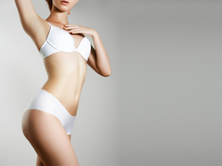Perfect slim toned young body of the girl. An example of sports , fitness or plastic surgery and aesthetic cosmetology