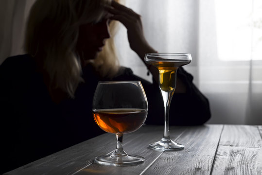 Woman drinking alcohol alone looking out her window. Depression, alcoholism, lonely person concept. Alcohol addiction and Social problem - with alcoholism and poisoning