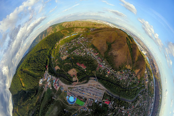Helicopter drone shot. Aerial photography of a modern city over an area, a large crossroads, high-rise buildings, a park and roads. Panoramic city 360  shot from above