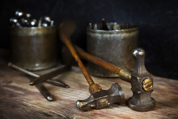 old vintage hammers and hallmark steel punches on a rustic wooden workbench of a goldsmith against a dark background