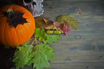 Pumpkin and autumn leaves on rustic wooden table