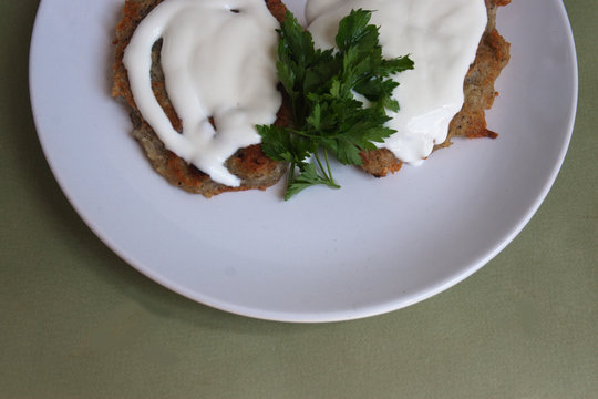 Potato pancakes with sour cream, parsley on a half  plate. Candid, view from above.