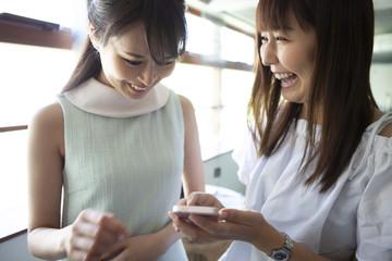楽しそうにスマートフォンを見ている女性たち
