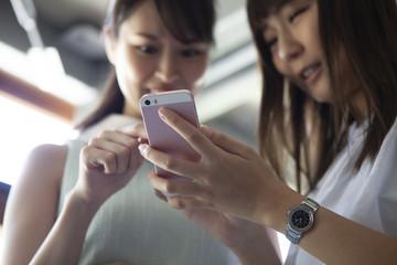 二人でスマートフォンに集中している女性たち