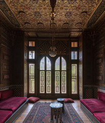 Historic Manial Palace of Prince Mohammed Ali. Small room at reception hall with ornate wooden wall and ceiling, decorated wooden windows, lantern and wooden floor, Cairo, Egypt