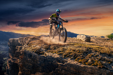 Mountain biker on sunset stone trail. Male cyclist rides the rock Wall mural