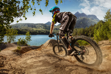 Mountain biker on forest trail near the lake. Male cyclist rides the rock