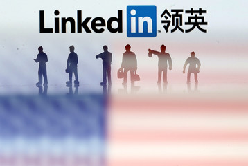 Small toy figures are seen between displayed U.S. flag and Linkedin logo in this illustration picture