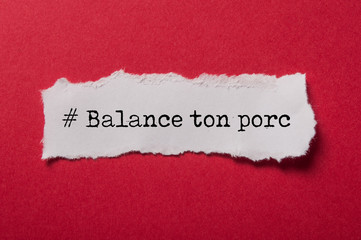 closeup of white torn paper on red paper background with text in french - # Balance ton porc, traduction :  denounce your pig