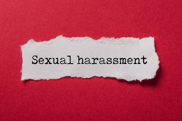 closeup of white torn paper on red paper background with text - Sexual harassment