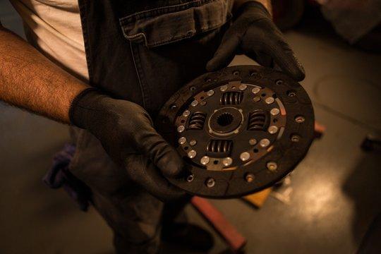 Male mechanic holding mac wheel