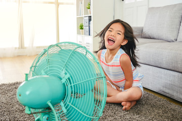 litle girl laughing and sitting in front of fan.