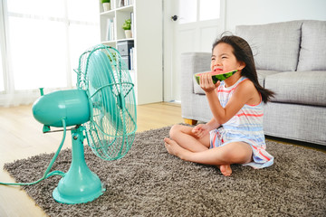 kid feeling cold while sitting in front of fan.