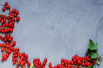 Food flatlay items. Red currant berries lying on gray concrete background. Top view