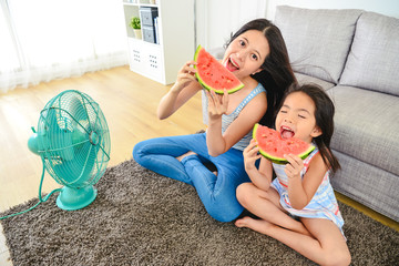 lovely mom and kid taking a big bite of melon.
