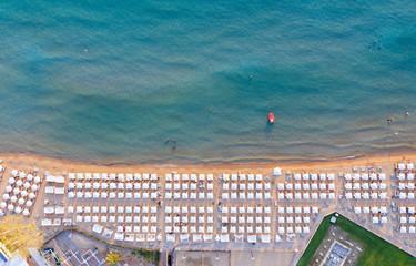 Wall Mural - Luftaufnahme des beliebten Astir Strand in Vouliagmeni, Athen, Griechenland, mit symmetrisch angeordneten Sonnenschirmen und Sonnenliegen