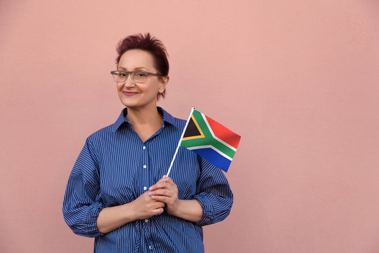 South Africa flag. Woman holding South Africa flag. Nice portrait of middle aged lady 40 50 years old with a national flag over pink wall background outdoors.