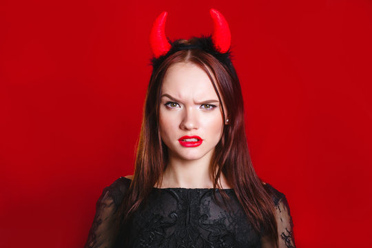 Sexy halloween woman devil on red background .