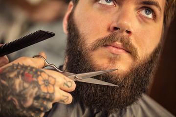 Barber with scissors shaving bearded.