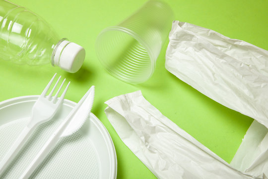 Plastic disposable utensils on green. fork, knives, plates, cups and a package, bottle,  bag