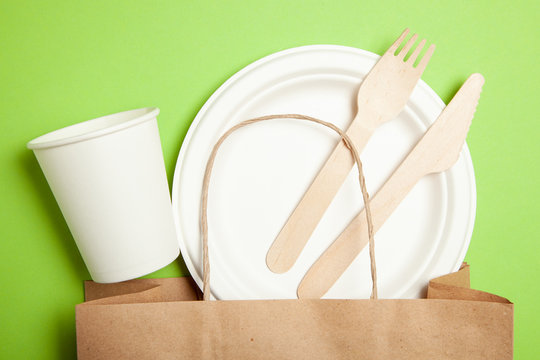 Eco-friendly disposable utensils made of bamboo wood and paper on a green. Draped spoons, fork, knives, bowls with cups and packet
