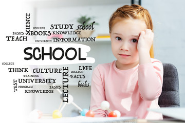 beautiful red haired schoolgirl looking at camera while studying with molecular model at home, with school word