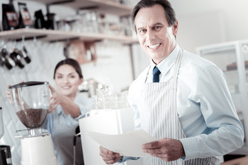 Holding documents. Cheerful successful cafe owner wearing an apron and holding documents while standing near his charming barista