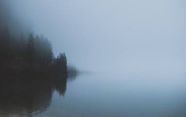 Mysterious mountain lake in early spring morning. Spooky dense fog covering the water. Sleepy misty landscapes in Alps, Austria.