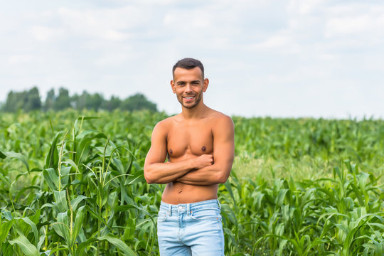 Young dark-skinned man smiles in light blue jeans in good physical shape stands in a rural spot in the green field of corn.