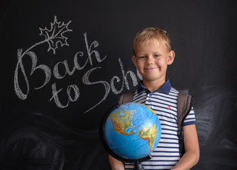 boy with a globe on the background of the school Board