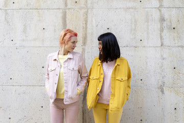 Two alternative friends having fun, wearing yellow and pink jeans clothes, face to face