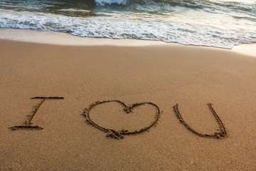 write I love you on the sand with the wave