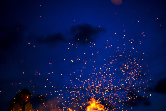 Large burning bonfire with soft glowing flame throws flying sparkles all around. Romantic summer evening, people relaxing and enjoying calmness at the seaside during the Night of ancient lights
