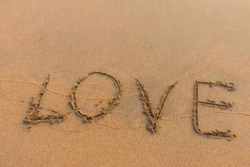 The word love written on the sand.