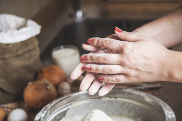 Female hands covered with flour above  bowl