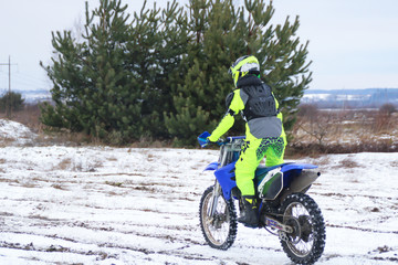 A man on a cross motorcycle trains in the winter in the snow