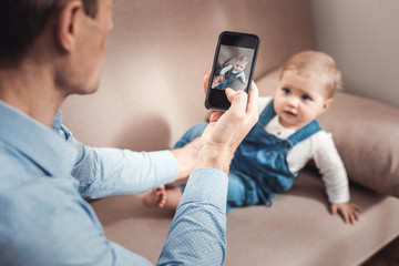 Digital device. Selective focus of a modern smartphone being in hands of nice loving father while taking photos of his child