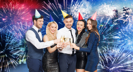 celebration and holidays concept - happy friends clinking champagne glasses at birthday party over firework lights background