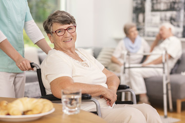 A geriatric female patient in a wheelchair with a health assistant in a lobby of a luxurious private rehabilitation clinic. Blurred background.