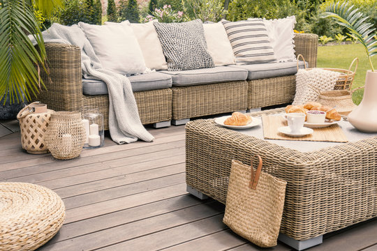 Wicker patio set with beige cushions standing on a wooden board deck. Breakfast on a table on a backyard porch.