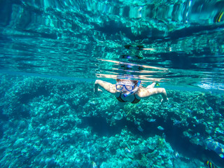 Girl swims near coral in red sea.