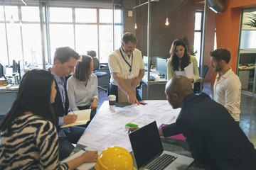 Business people discussing over blueprint in the meeting