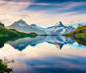 Colorful summer sunrise on Bachalpsee lake with Schreckhorn and Wetterhorn peaks on background.
