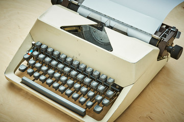 bright old typewriter with gray keys on a wooden table